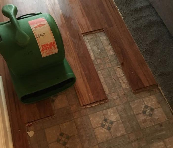 Tile floor and laminate floorboards with SERVPRO drying equipment