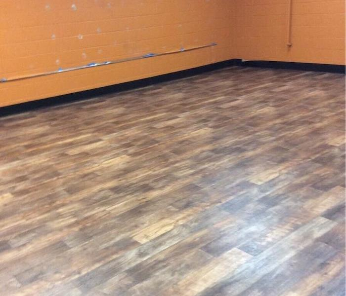 Gym with laminate flooring and cinder block wall