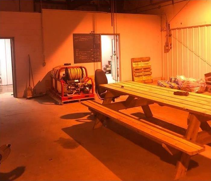 picnic table inside warehouse; doors to offices shown