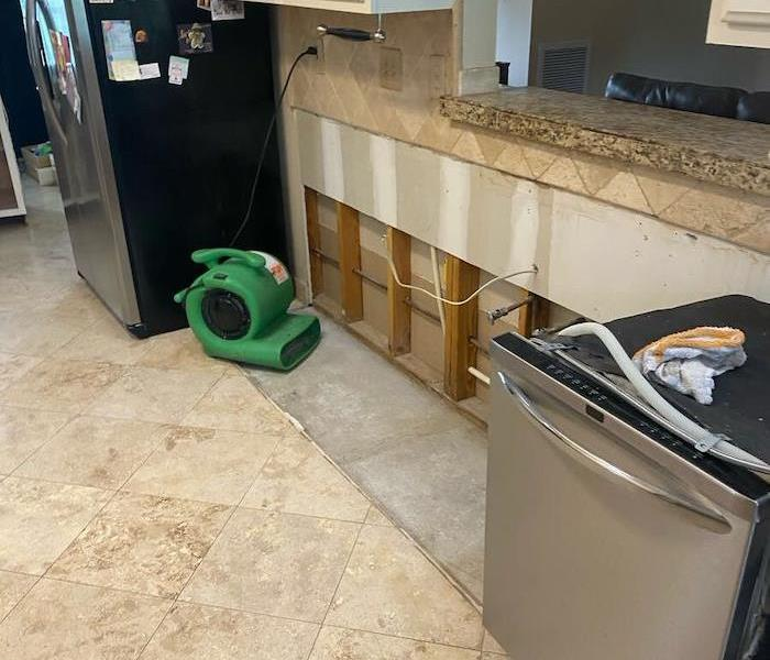 Kitchen with SERVPRO drying equipment on exposed cabinet wall