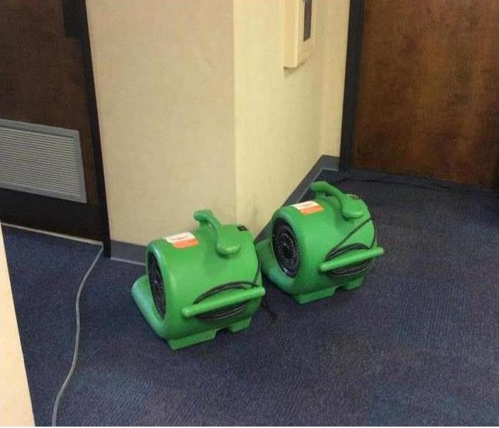 Air movers drying wet carpet
