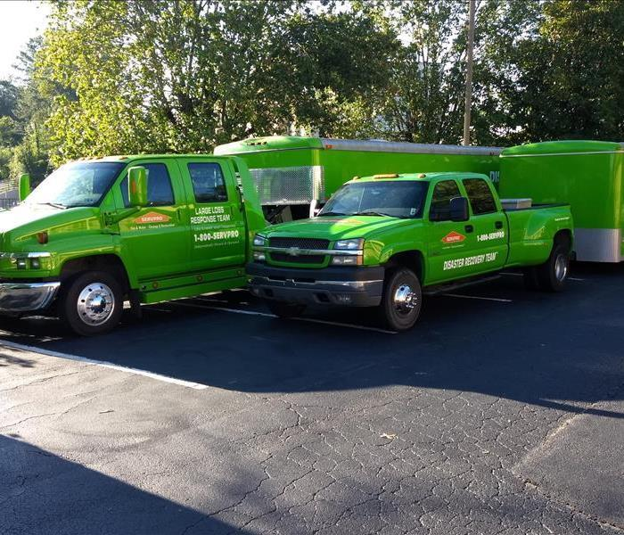Green SERVPRO trucks with trailers in a parking lot