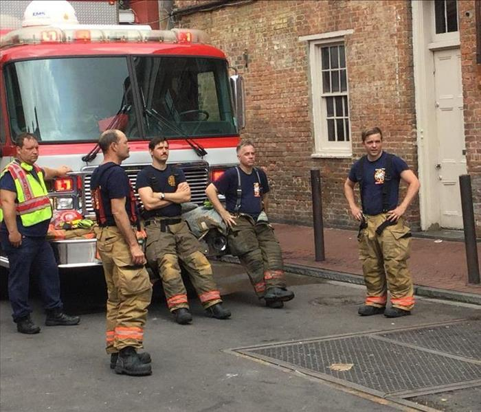 Firemen Hanging out by a Fire Truck in front of the FireHouse