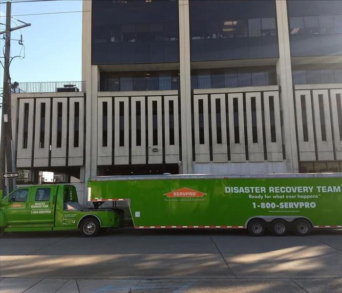A SERVPRO truck and trailer in front of a building.