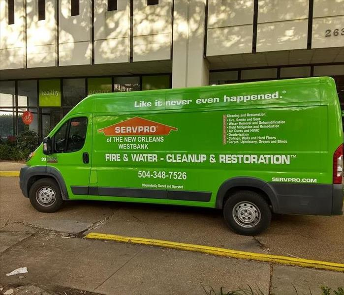 green SERVPRO van parked at job site